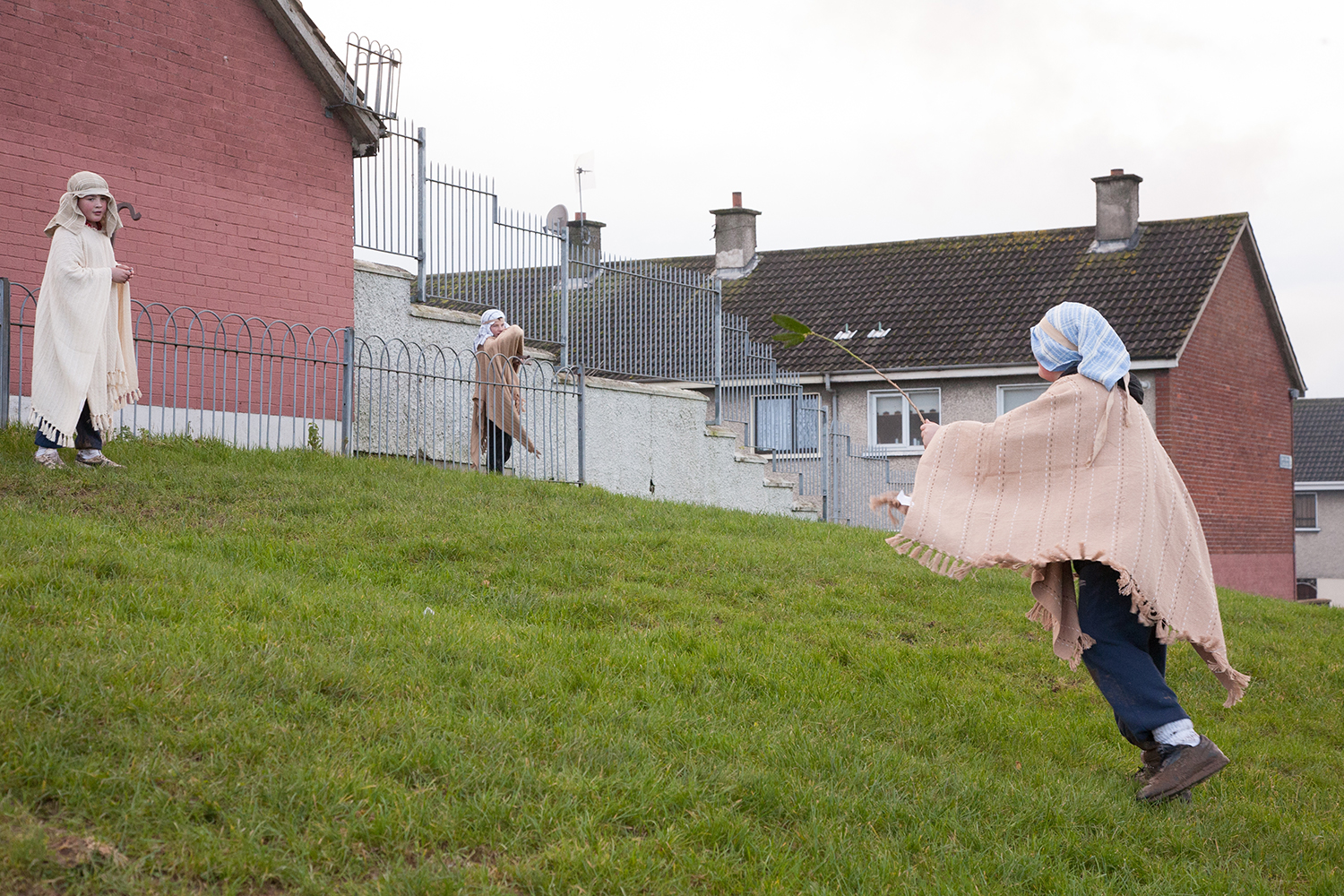A documentary photograph of three boys playing before they help perform a live nativity scene with monks in Moyross, Limerick, Ireland