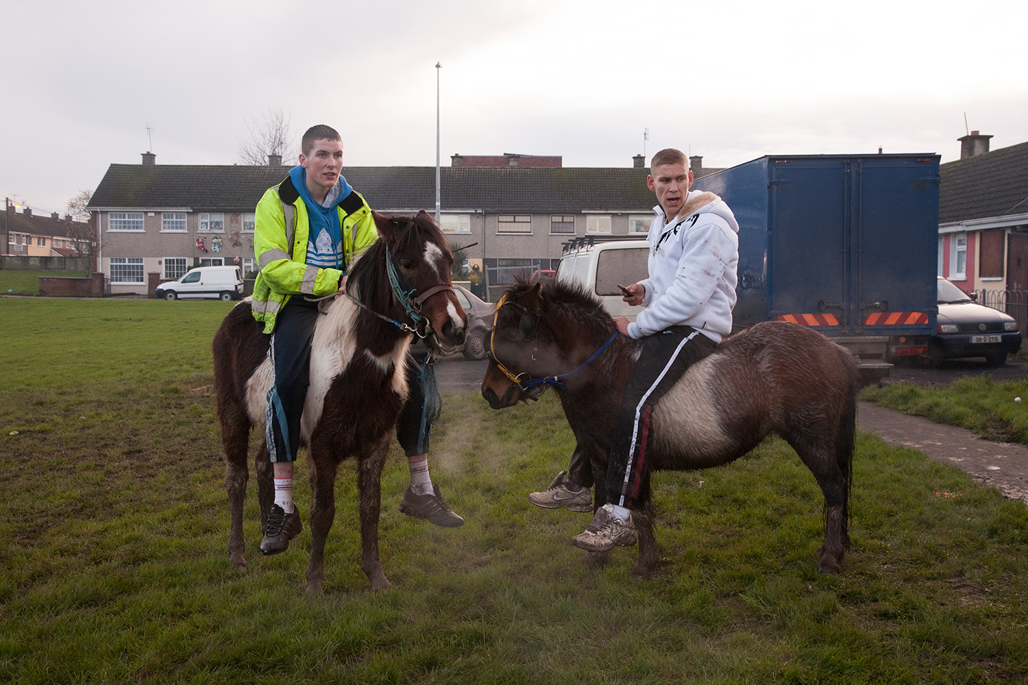 A documentary photograph of two older teenager boys sitting on ponies in moyross, Limerick, Ireland