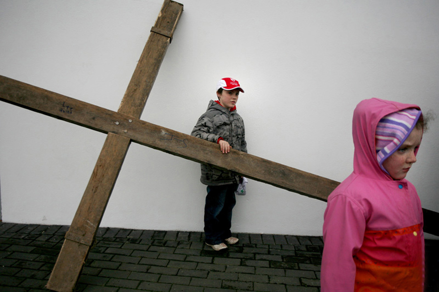 A documentary photograph of two kids standing by a large crucifix before the monks of Moyross perform the passion of the christ in Limerick, Ireland