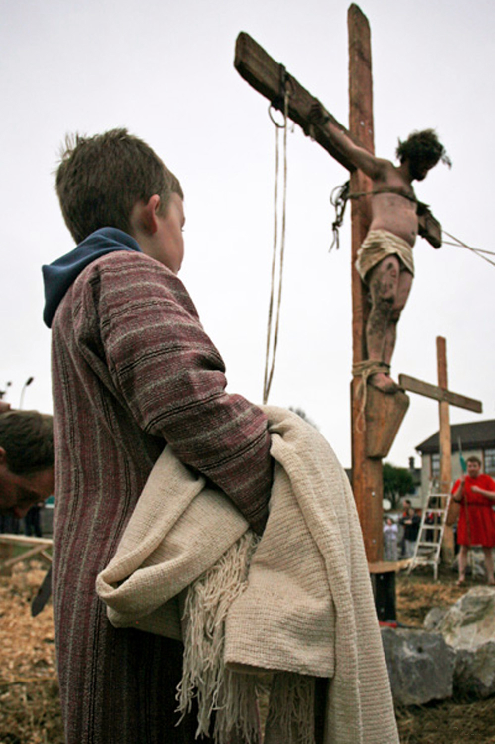 A documentary photograph of boy watching Jesus hang on a crucifix while the monks of Moyross perform the passion of the christ in Limerick, Ireland
