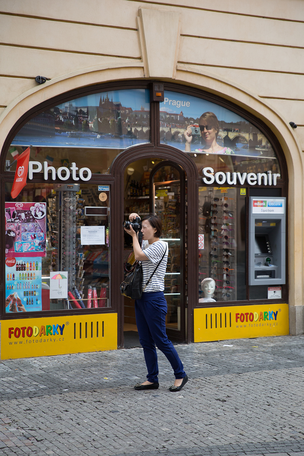 A documentary photograph of a tourist taking a photograph outside a photo and souvenir shop in Prague, Czech Republic