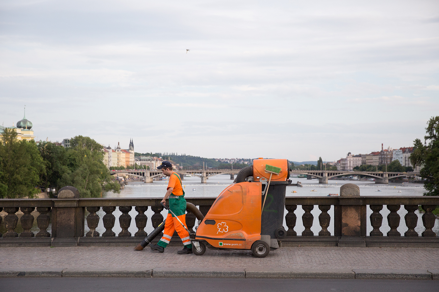 A documentary photograph of a worker cleaning the sidewalk of Prague with an industrial orange vacuum in Czech Republic
