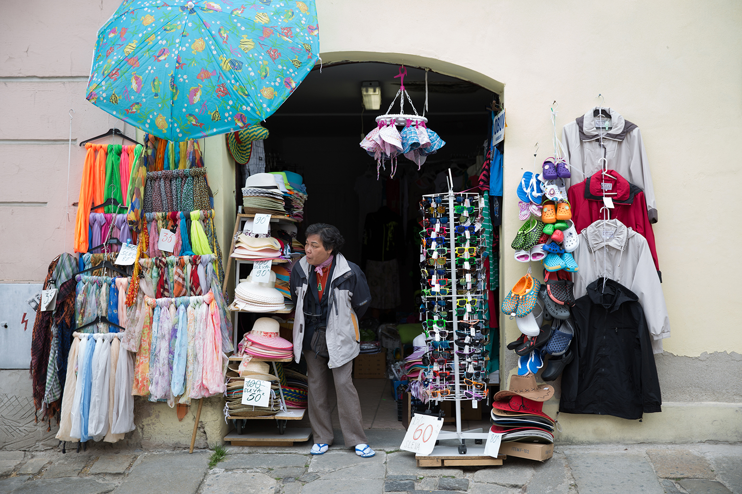 A documentary photograph of a shop owner looking for customers outside her shop in Cesky Krumlov, Czech Republic