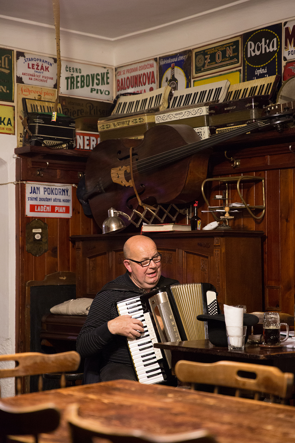 A documentary photograph of a man playing an accordion at a bar in cesky krumlov, Czech Republic