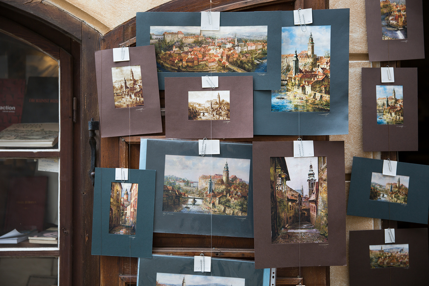 A documentary photograph of paintings of czech republic being sold at a tourist stand in Prague