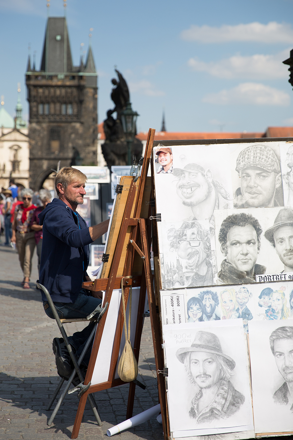 A documentary photograph of an artist drawing portraits for tourist on the bridge in Prague, Czech Republic