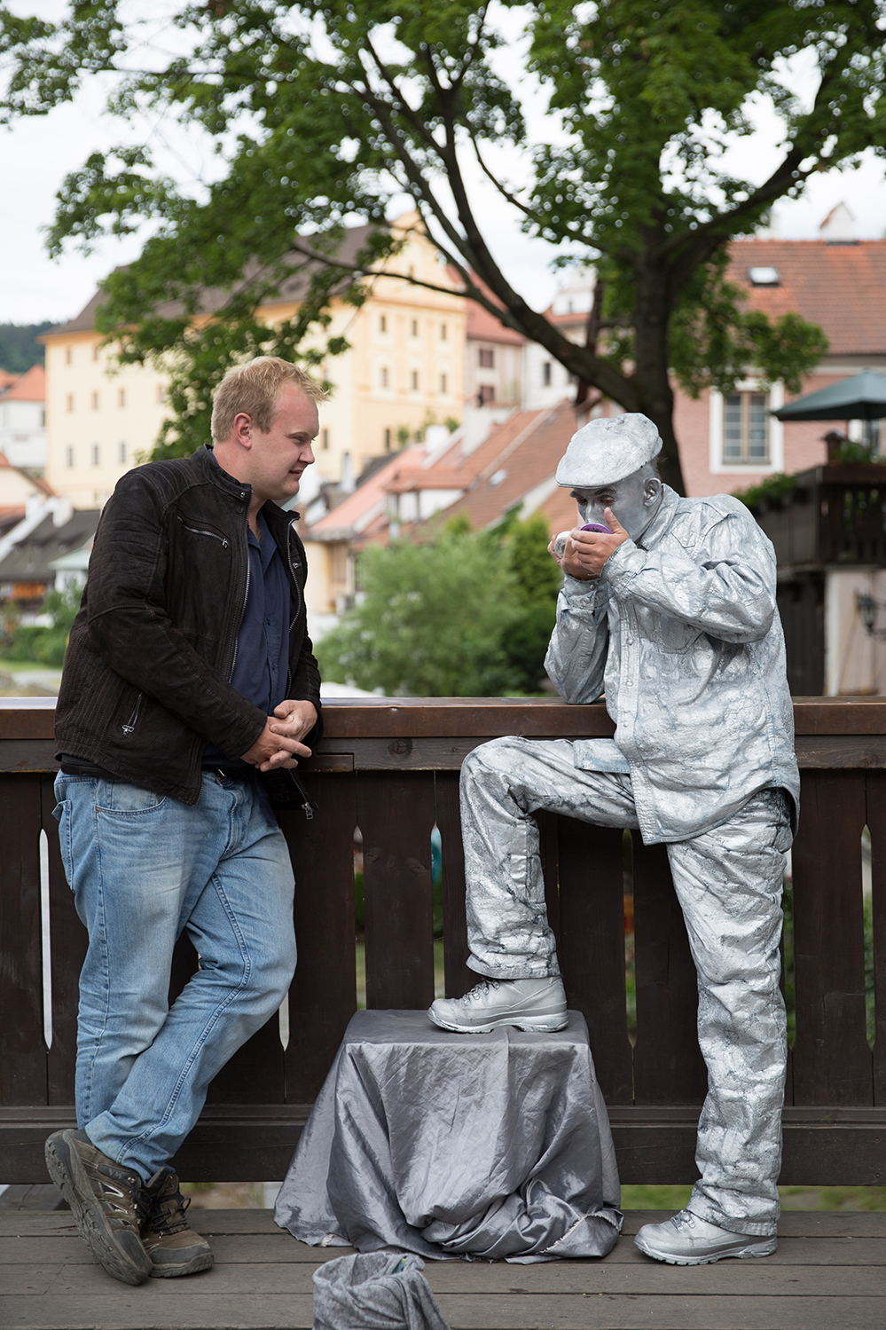A documentary photograph of a man talking to human statue as he looks at himself in the mirror in cesky krumlov, Czech Republic