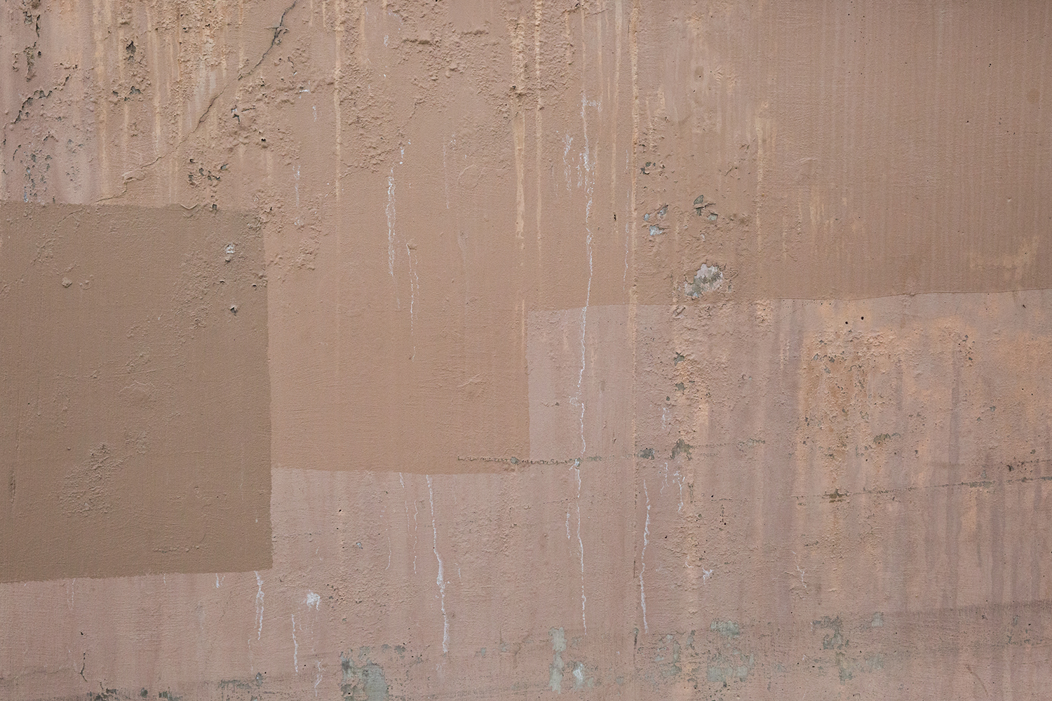 A detailed photograph of a wall with chipped and mismatched paint