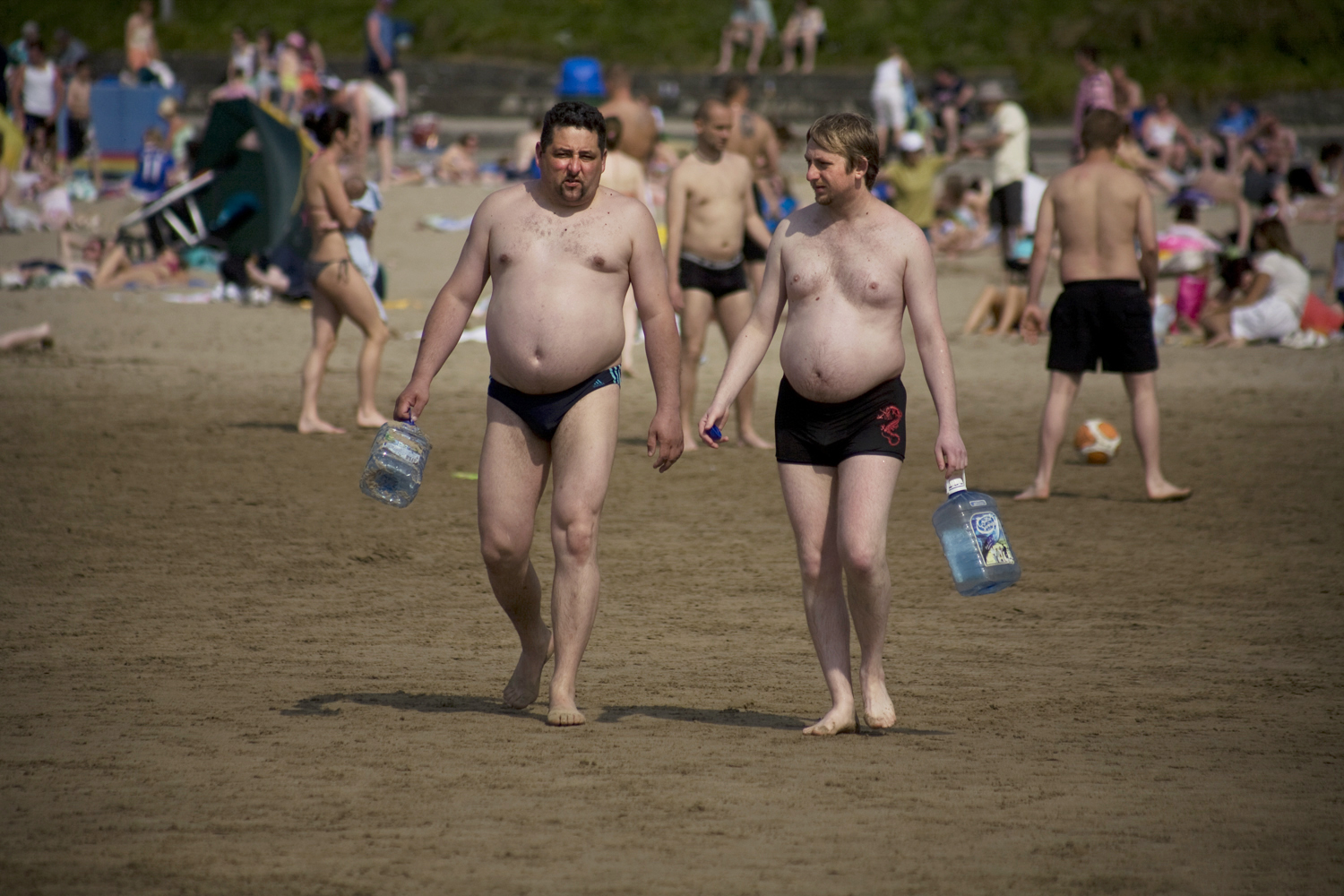 A documentary photograph of two men walking along an irish beach holding empty water jugs