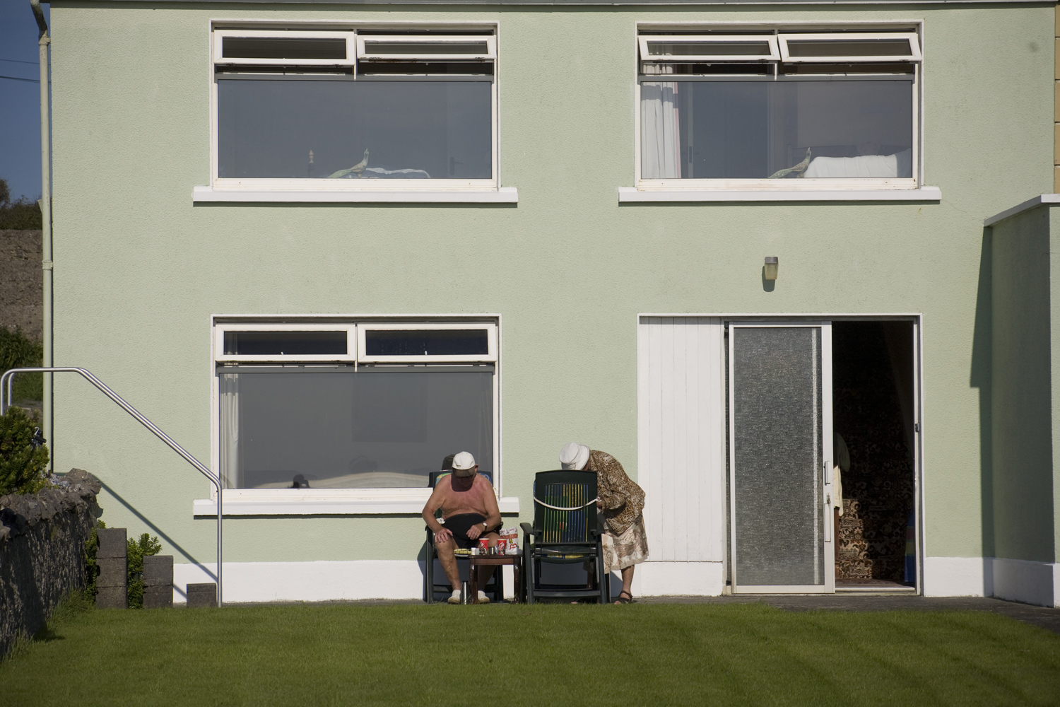 A documentary photograph of an elderly couple sitting outside their home during a rare sunny day in ireland