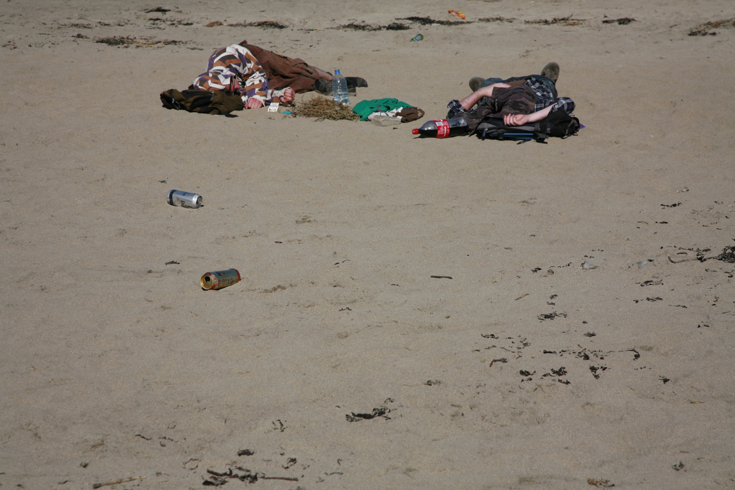 A documentary photograph of two hung over men laying on an irish beach with empty cans around them