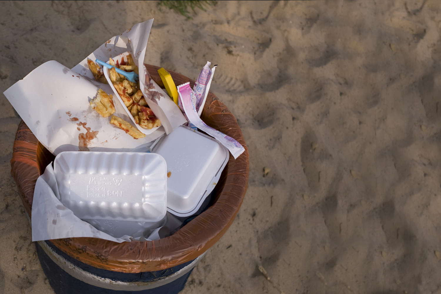 A documentary photograph of chips in bin on an irish beach