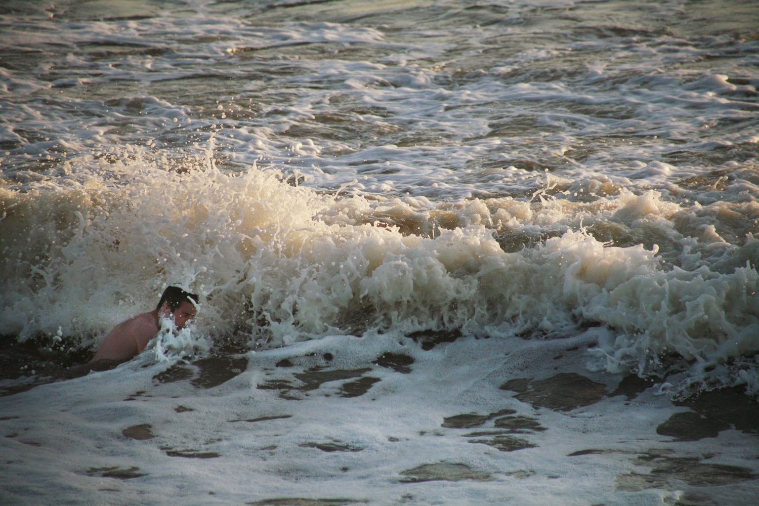 A documentary photograph of a man swimming in the ocean in Ireland