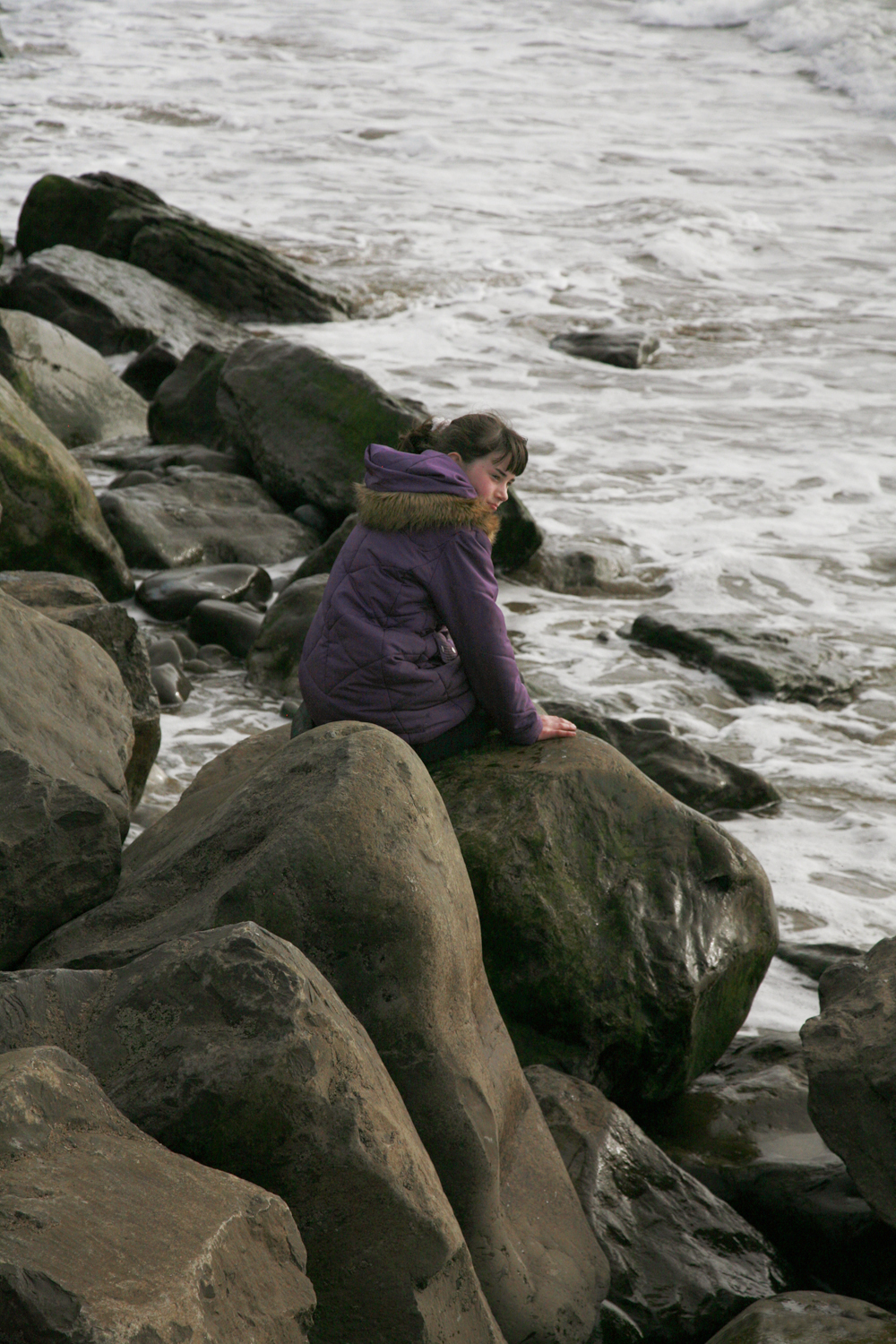 A documentary photograph of a girl sitting on the rocks of an Irish beach with a winter coat on