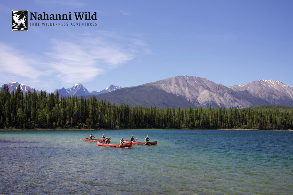 Download     Caption:  Paddlers descending on Nahanni River on a vibrant June day.   Photographer:  Joel Hibbard   Location:  Nahanni River, Nahanni National Park (the 1st UNESCO World Heritage Location)