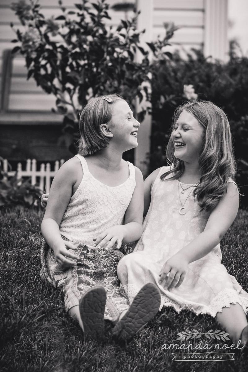 sisters-in-yard-laughing-joke-black-and-white