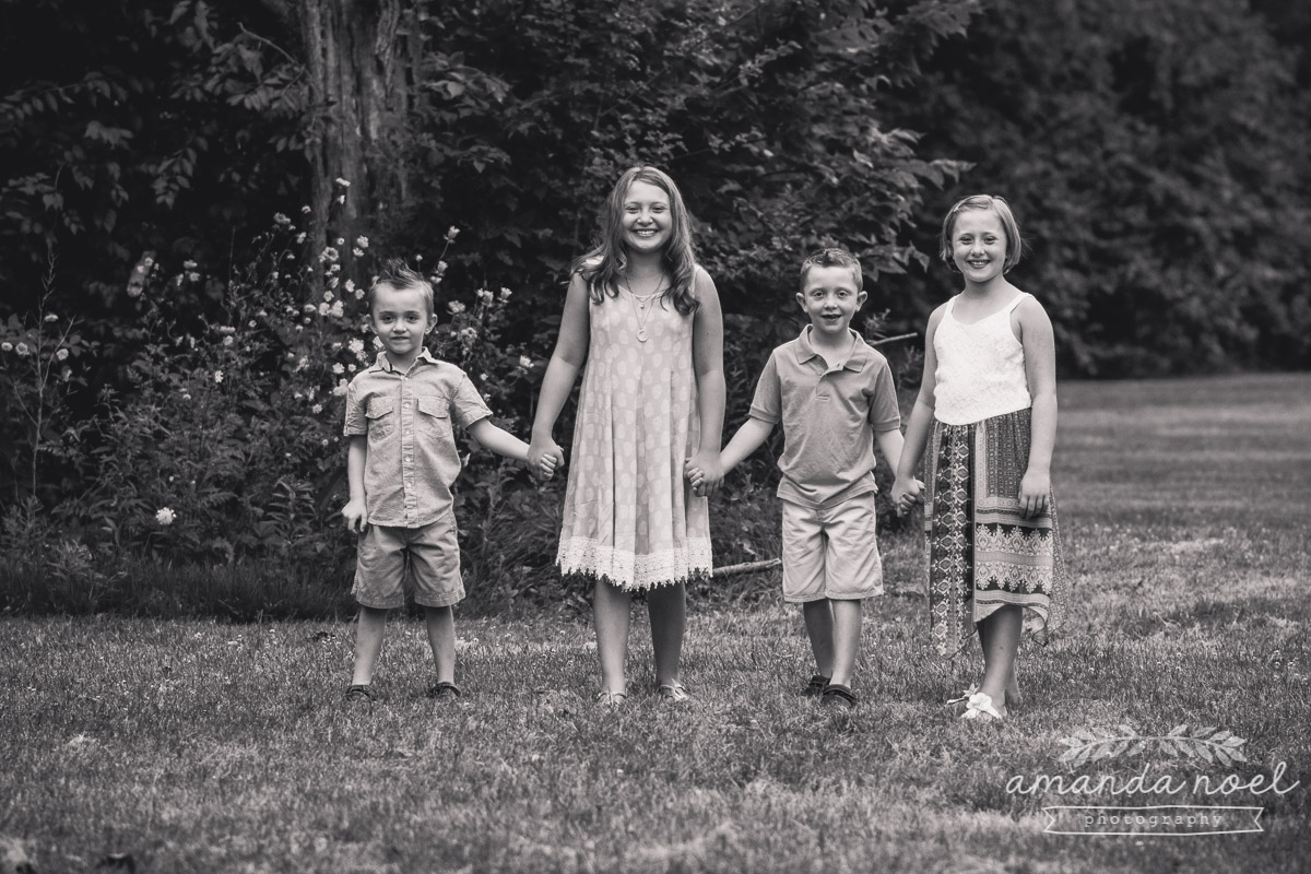 4-siblings-holding-hands-in-field-black-and-white