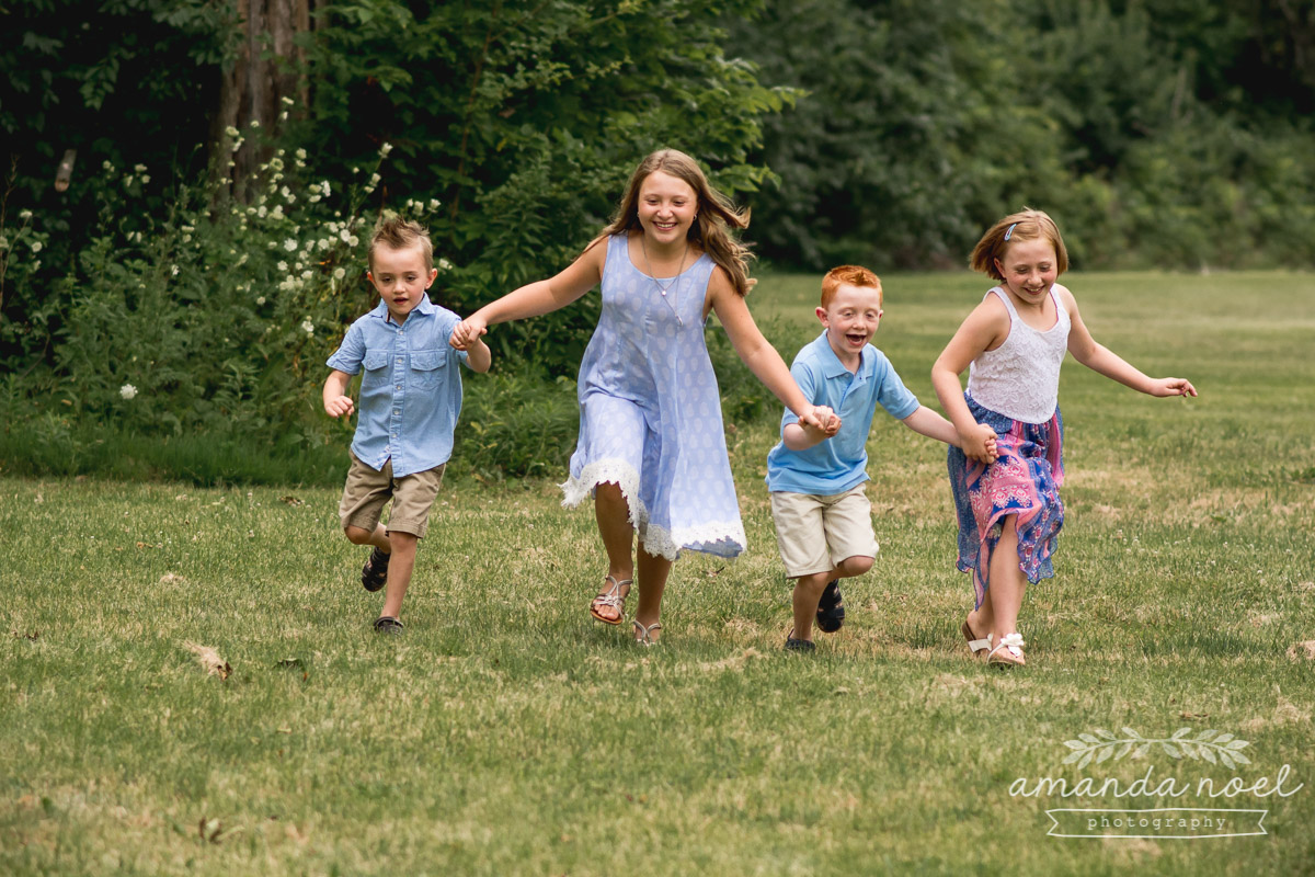 4-siblings-in-blue-holding-hands-running-in-Springfield-Ohio-field