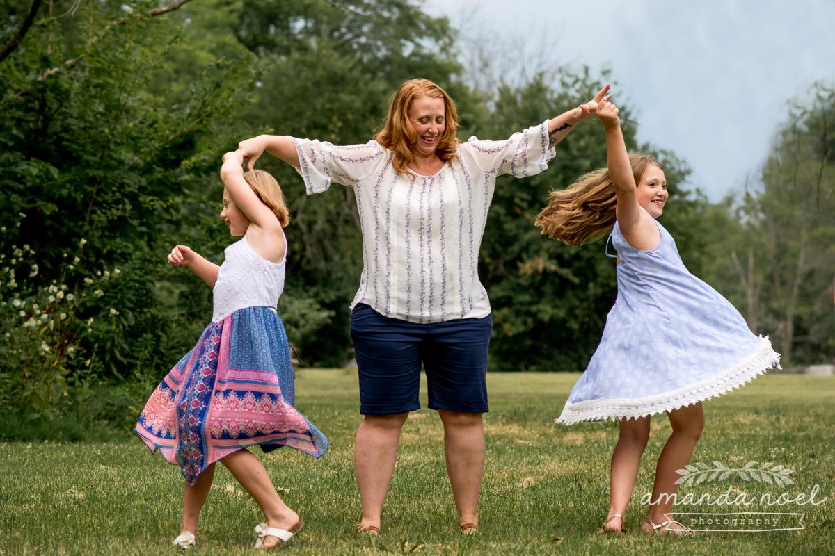 redhead-mom-daughters-dance-twirl-in-field
