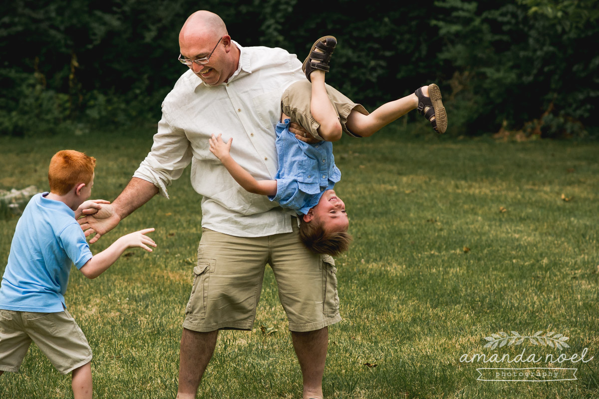 dad-sons-boys-in-blue-wrestle-in-field
