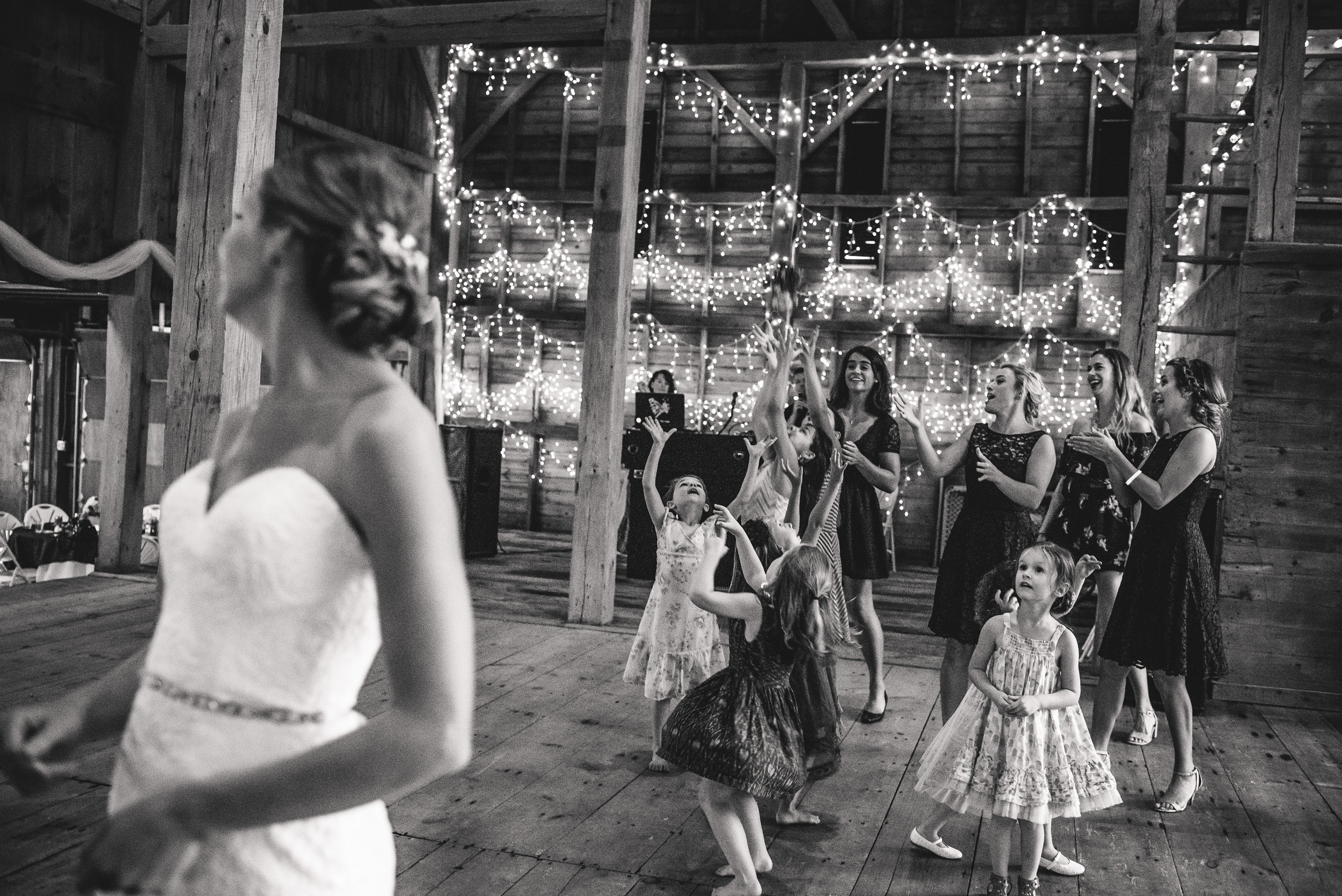 bouquet toss in barn black and white