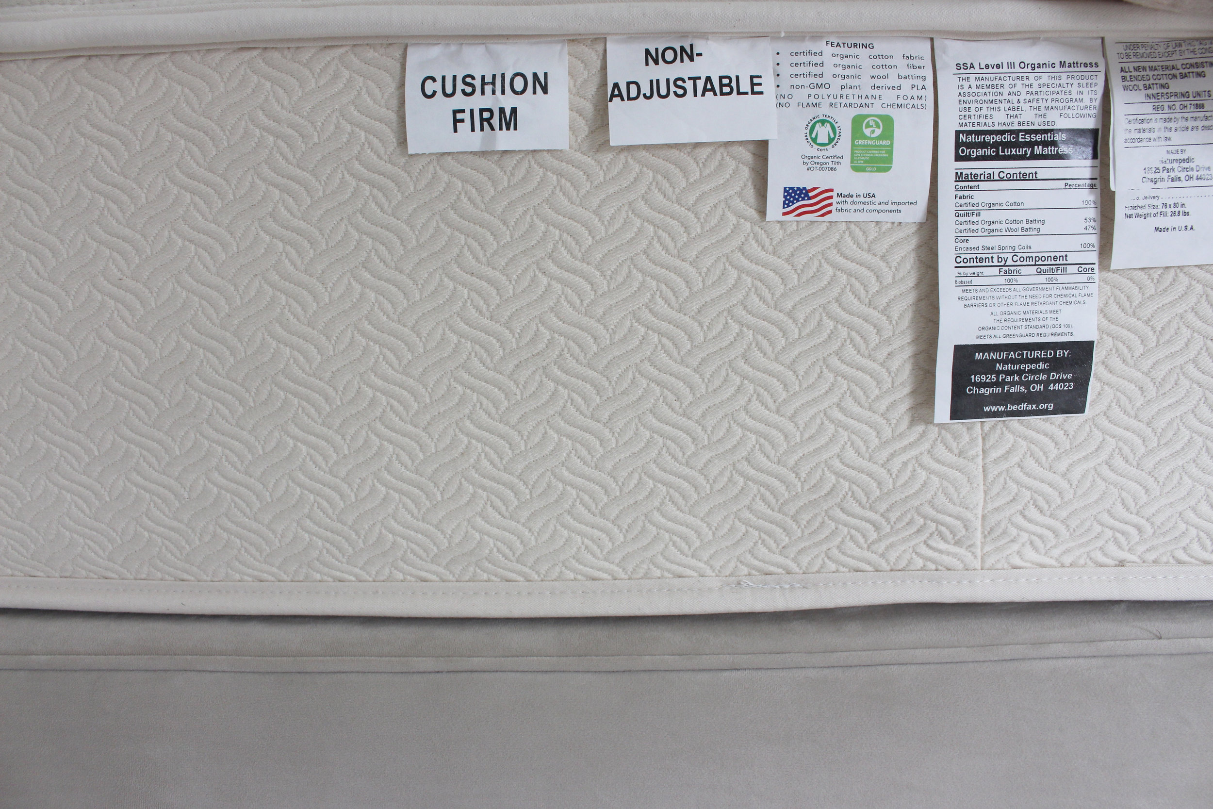 A photo of our cushion firm Naturepedic mattress under the cover.