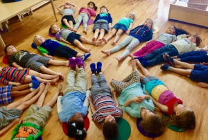 Research suggests that school-based yoga cultivates competencies in mind-body awareness, self regulation and physical fitness leading to improvements in students' behavior, mental state, health and performance, as well as teacher resilience, effectiveness and overall classroom climate.