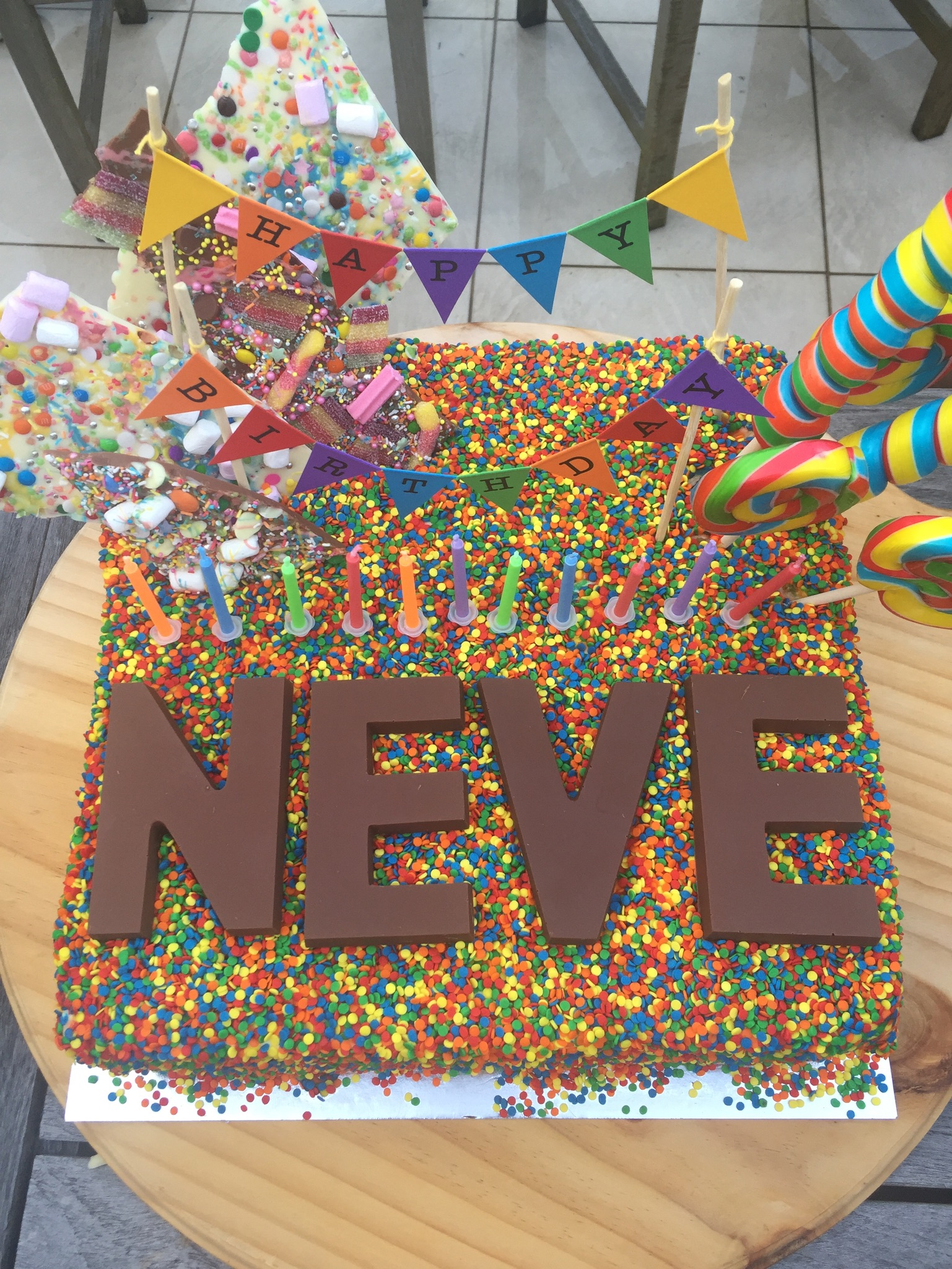 A Rainbow Layered Birthday Cake with Sprinkles and Chocolate Letters for Neve's Rainbow Unicorn Themed Birthday Party | Be inspired by this Rainbow Unicorn Themed Pool Party, created by The Real Housewives of Sydney's Nicole O'Neil for her daughter Neve's 11th Birthday. Featuring a beautiful rainbow snack bar, rainbow sprinkle cake and much more.