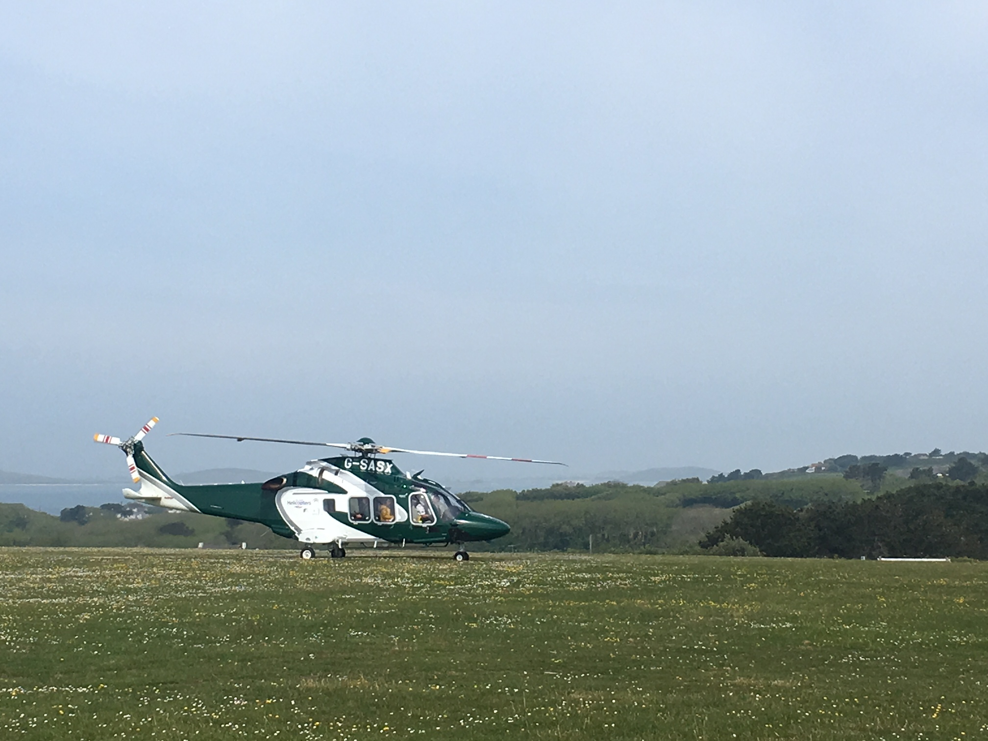 Island Helicopters 10-seater AW169 aircraft touching down at St Mary's Airport.