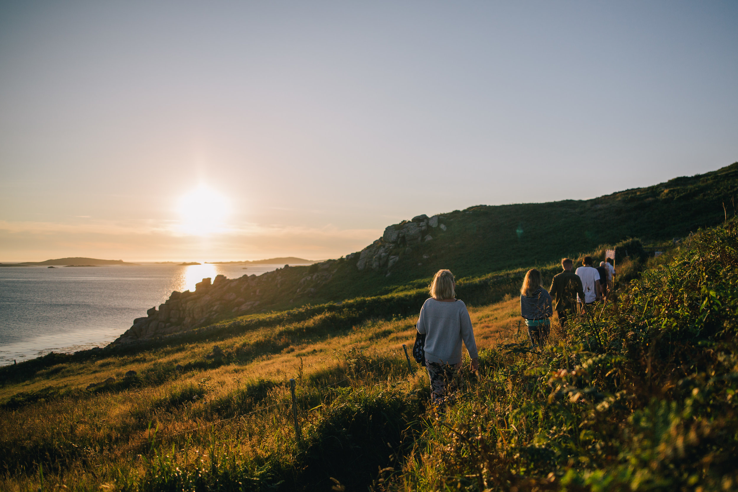 Walkers heading round St Mary's at sunset. Image courtesy of Islands' Partnership.
