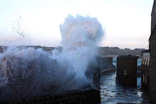 Waves crashing over St Mary's Quay. Image courtesy of This Is Scilly.