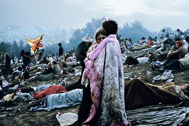 "Burk Uzzle's iconic Woodstock photo is of a couple wrapped in a blanket, embracing each other at dawn, oblivious to the camera and the chaos surrounding them. He didn't speak with his subjects, but they were later identified as Nick Ercoline and Bobbi Kelly — who at the time had been dating for just 10 weeks, but now have been married for 47 years.  Uzzle took the picture in the early hours of Sunday morning. He woke up around 4:30 a.m. and was walking around, looking for interesting subjects, being careful not to burn through his film too quickly. When he spotted the couple from a distance, he checked the light and zone-focused for a distance of 15 feet. His mentor, Henri Cartier-Bresson, had told Uzzle to study the Quattrocento painters for their detailed compositions, and that homework paid off: ""I walk up and I know the curvature of the hill has to work with the curvature of the heads. And there's the flag, it's going to have to be there, and just enough of the people."" He took a few frames in black and white before switching to color. Five decades later, Uzzle still remembered the details, down to the f-stop of 1.4: ""Very slow shutter speed, almost dark, holding myself very still, maybe a 15th of a second, and I was lucky that it was still sharp. But I was not high! So I was able to make the composition and be in focus and take the picture. And then I turned around to find something else to shoot."" From ""The Man Who Photographed Woodstock's Most Iconic Couple"" by Gavin Edwards for the New York Times . . . . . . #music #woodstock #newyork #festival #icon #photography #photooftheday #henricartierbresson #portrait #hippies #story #stories #thestorybar"