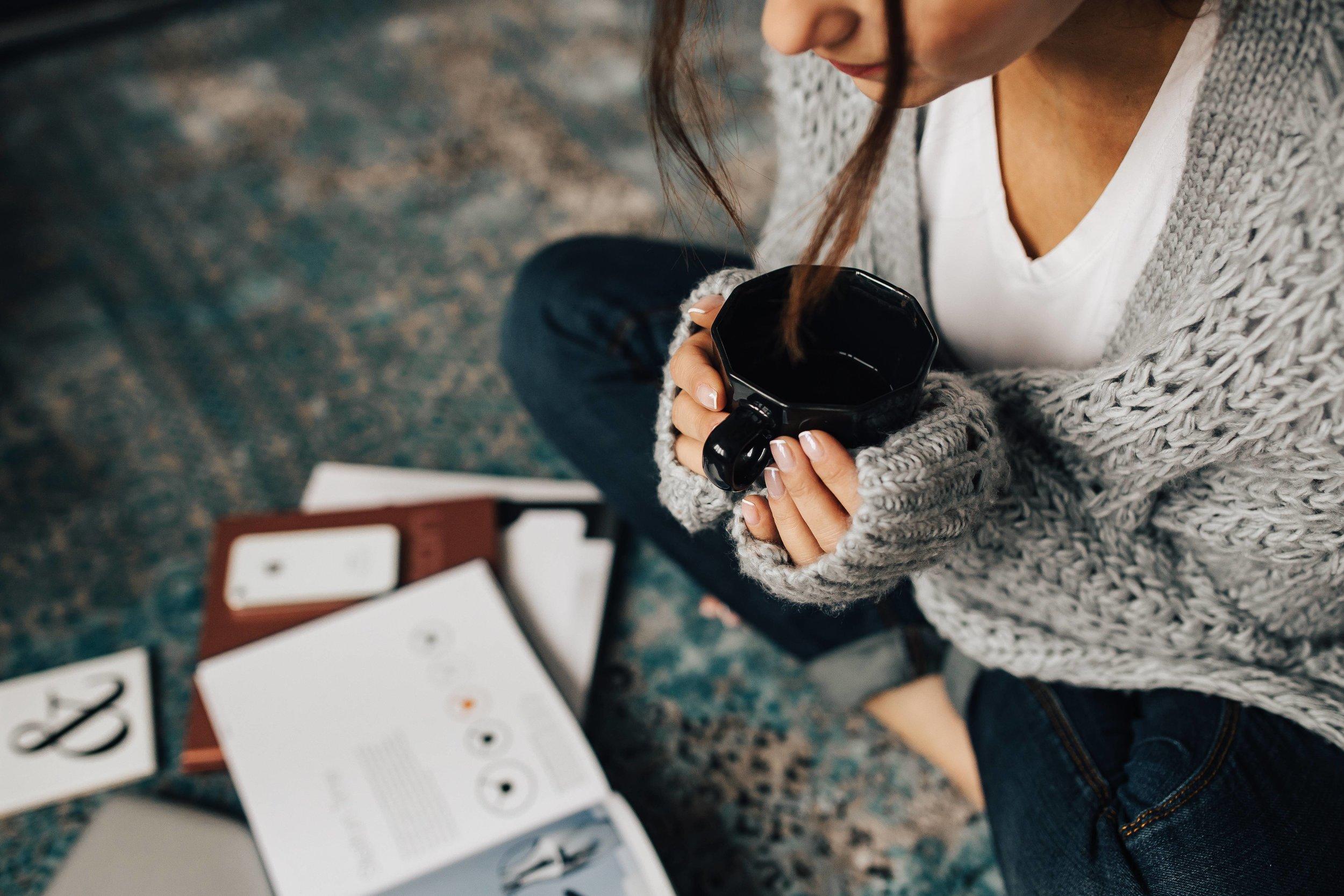 kaboompics_Woman reading magazines on the floor while enjoying hercup of tea.jpg