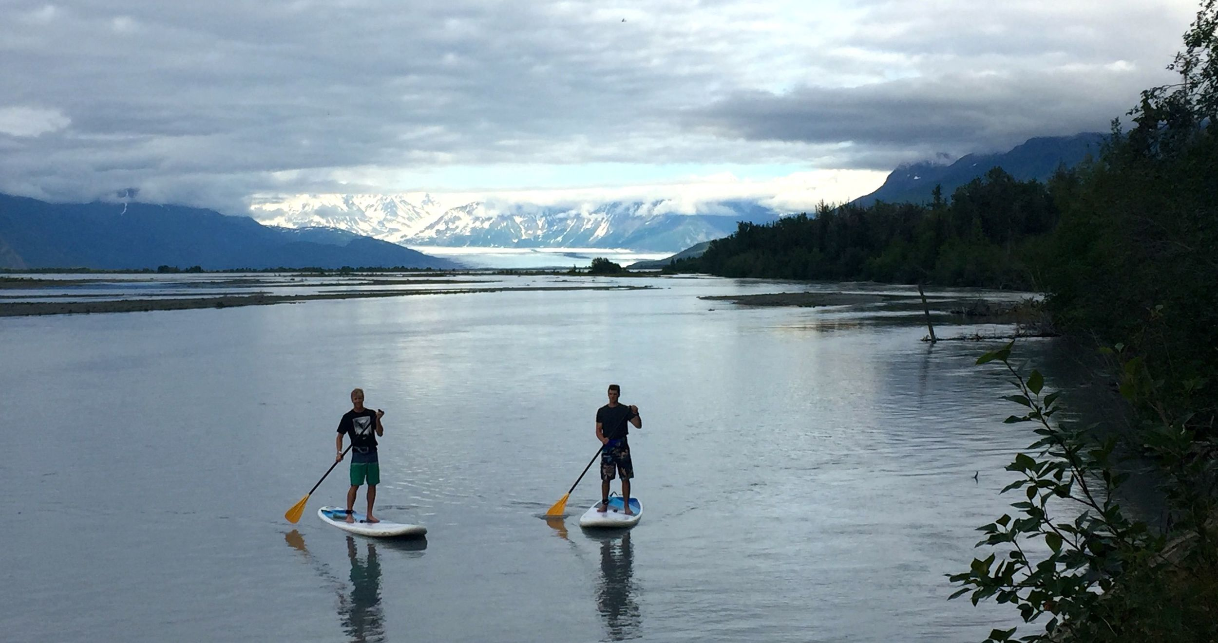 Erik and Jo taking a trip down the river on paddle boards.