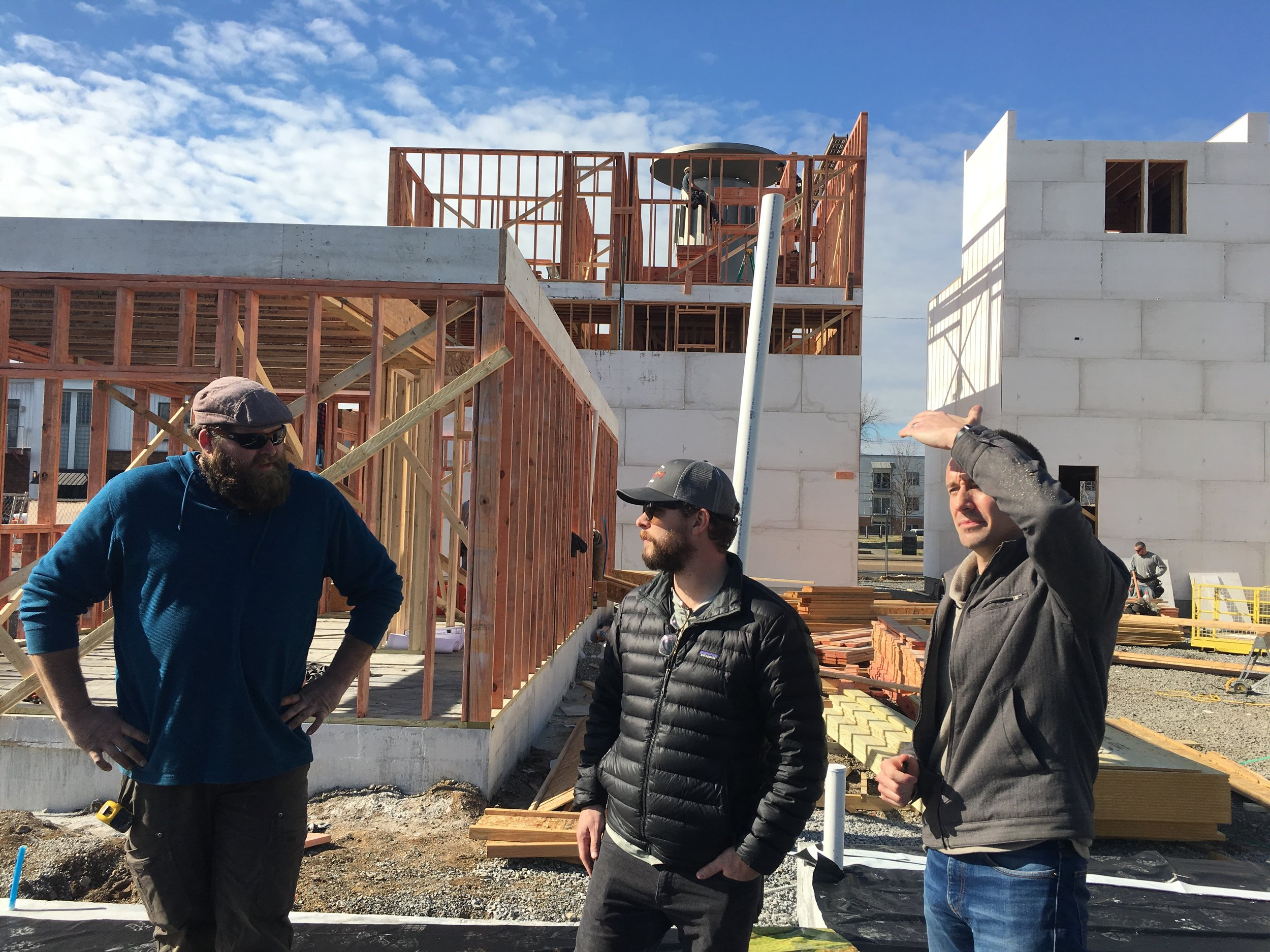 Thomas (center) and his site manager, Dan (left) discuss construction progress with Project Architect, Jared Hueter (right)