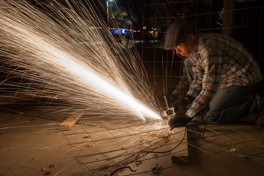 Cutting mesh at night with an angle grinder.