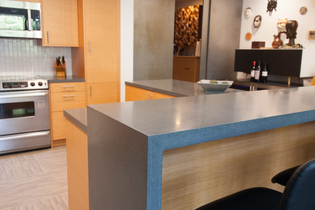 Waterfall edges finishes off the bar height counter area, designed to perch over a multi-functional workspace/mobile kitchen island.