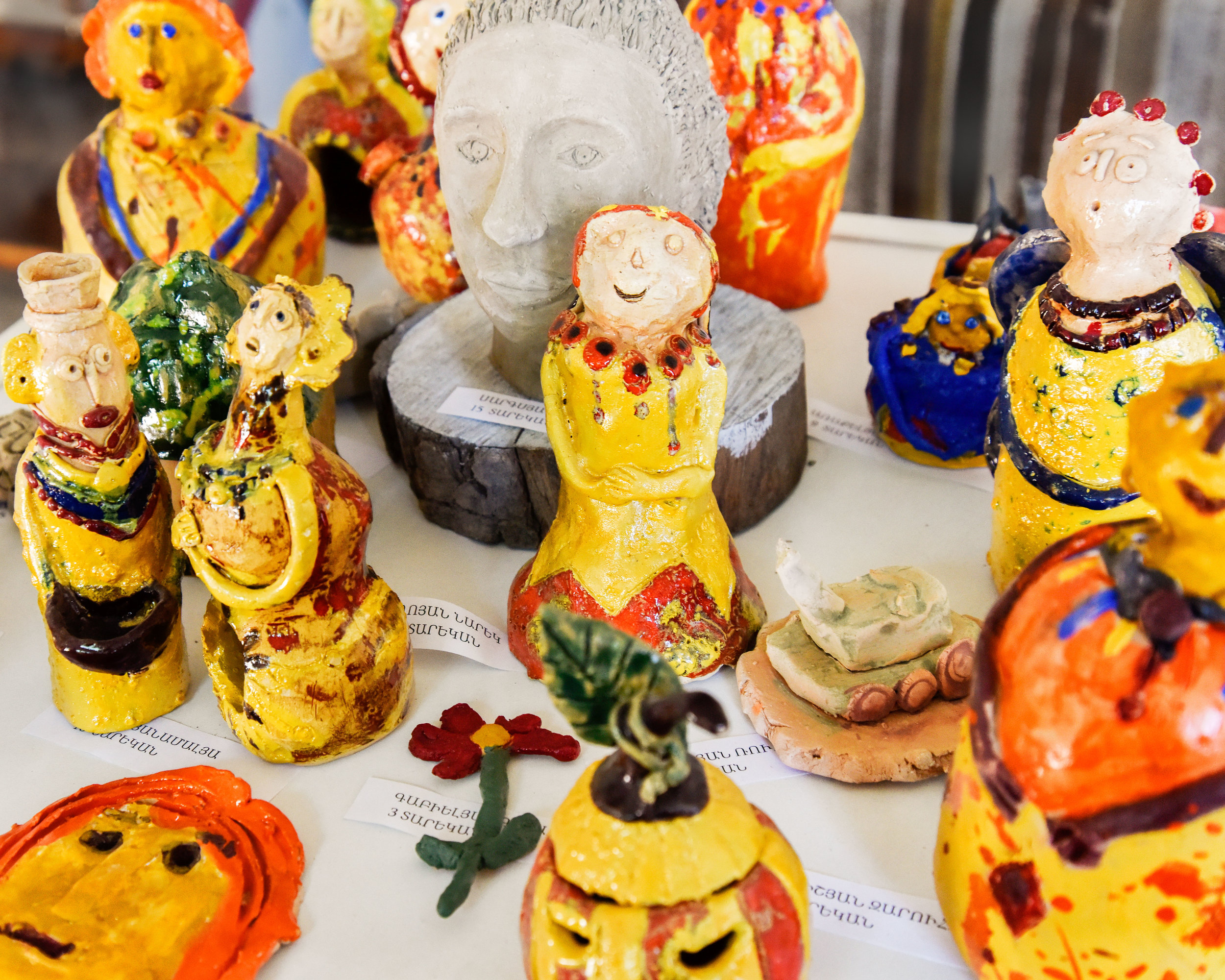 Handmade ceramic figures in traditional dress in the shop selling the student artists' work.