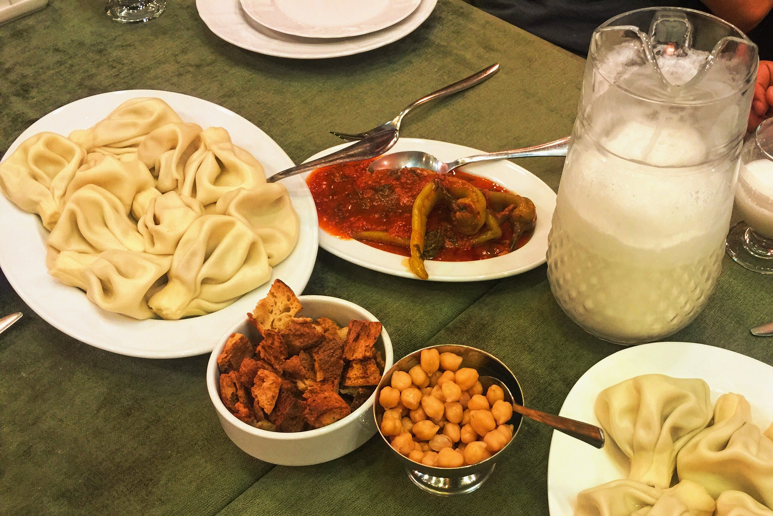 Platters of khinkali, condiments, chiles in tomato sauce, and tan to drink