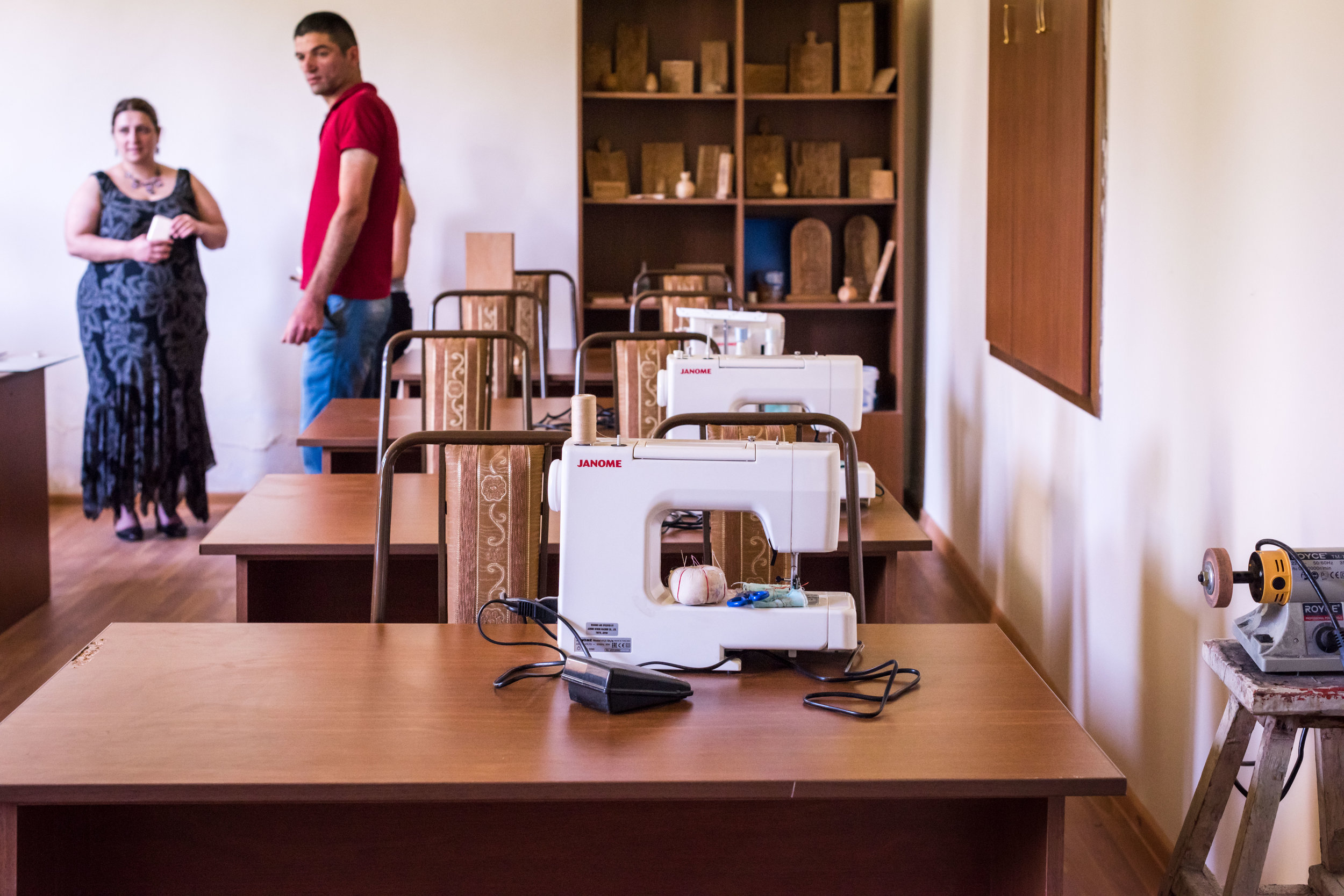 This is Chinchin's hobby group skills center where children learn woodcarving and sewing. Lusine Grigoryan discusses the progress of the center with Sarkis, evidenced by the lovely carved items displayed on the shelves.