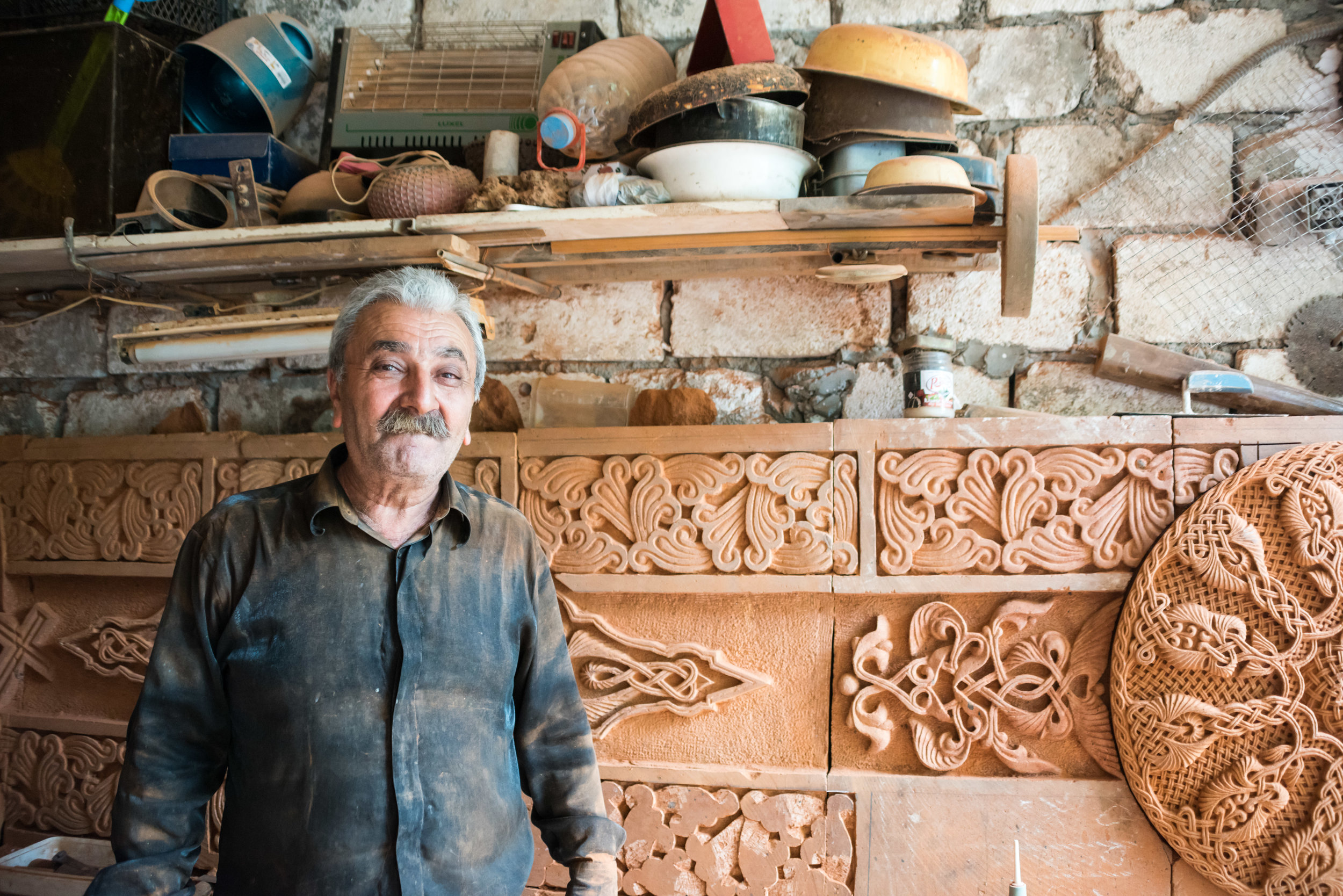"Master carver Sergey Hamzoyan in his Stepankert studio with work in progress for the main cathedral under restoration.  ""It is my soul's duty,"" says Mr. Hamzoyan."