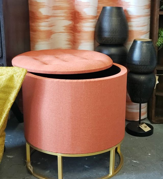 We love a good storage piece that provides both function and style like this orange ottoman