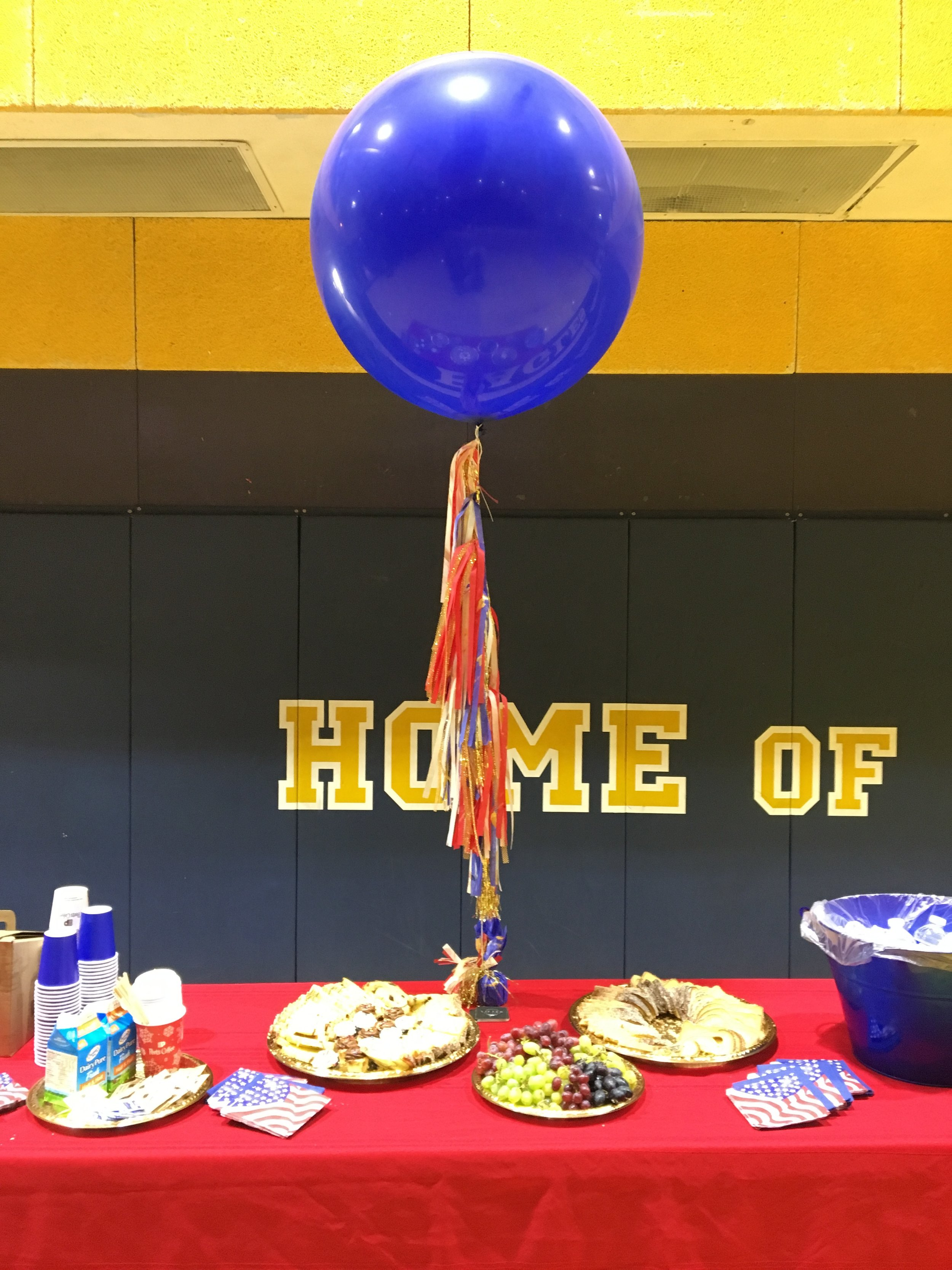 The giant, royal blue, luxury balloon hovers like fireworks above a sweet spread.