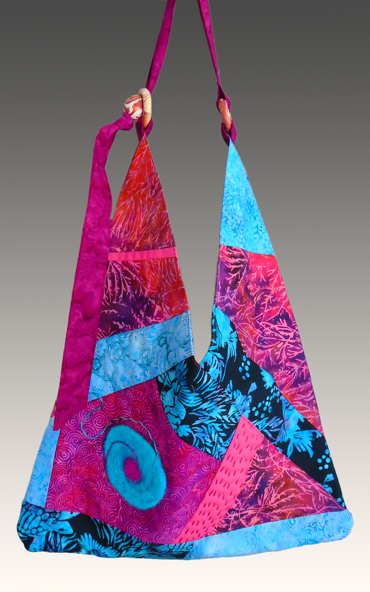 Tote bag with pieced Indonesian batiks, surface embroidery, hand-felted medallion, and hand-marbled wood hardware.