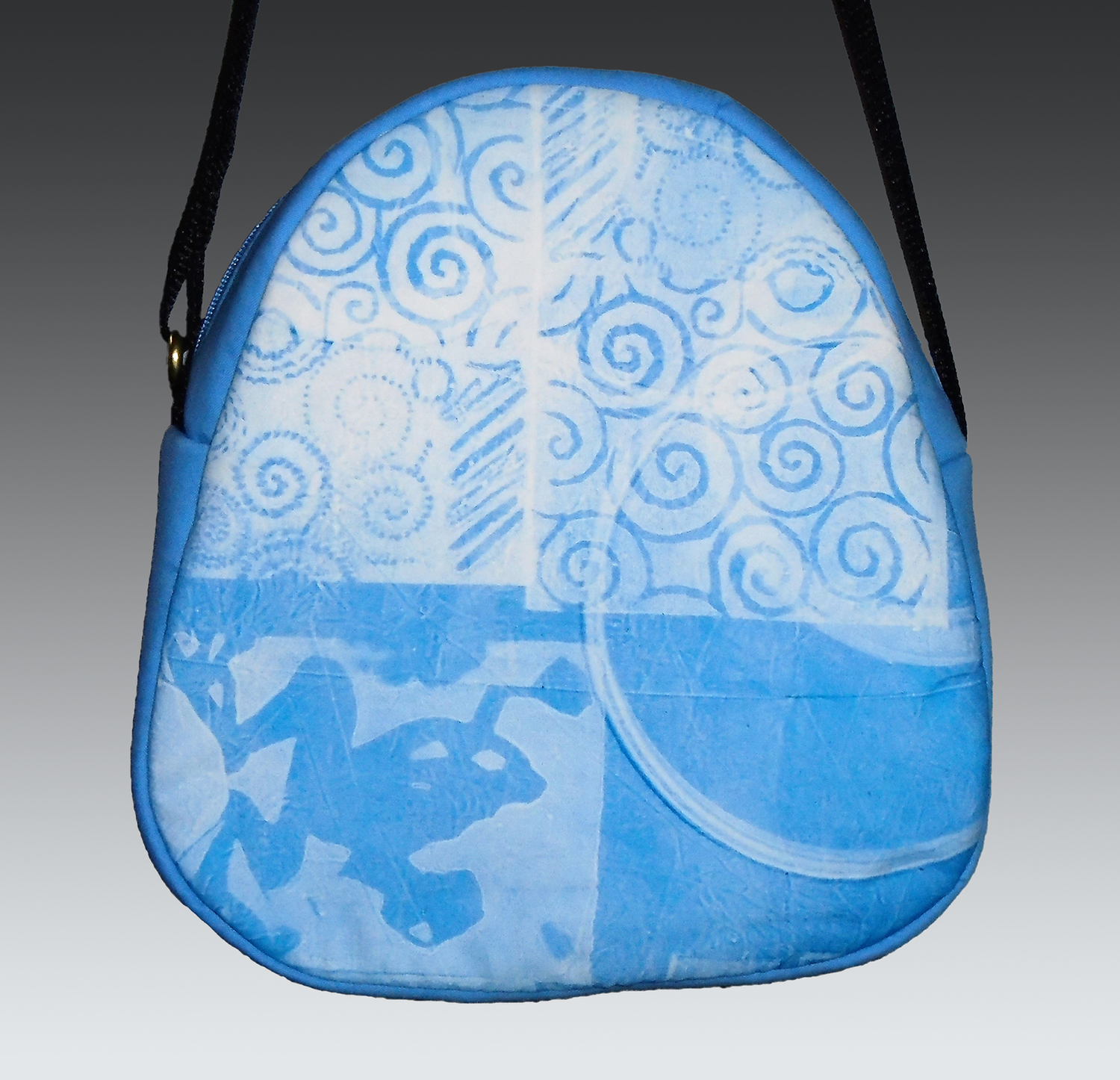 Crossbody zippered teardrop bag with monoprinted fabric panel; adjustable strap and inside pocket