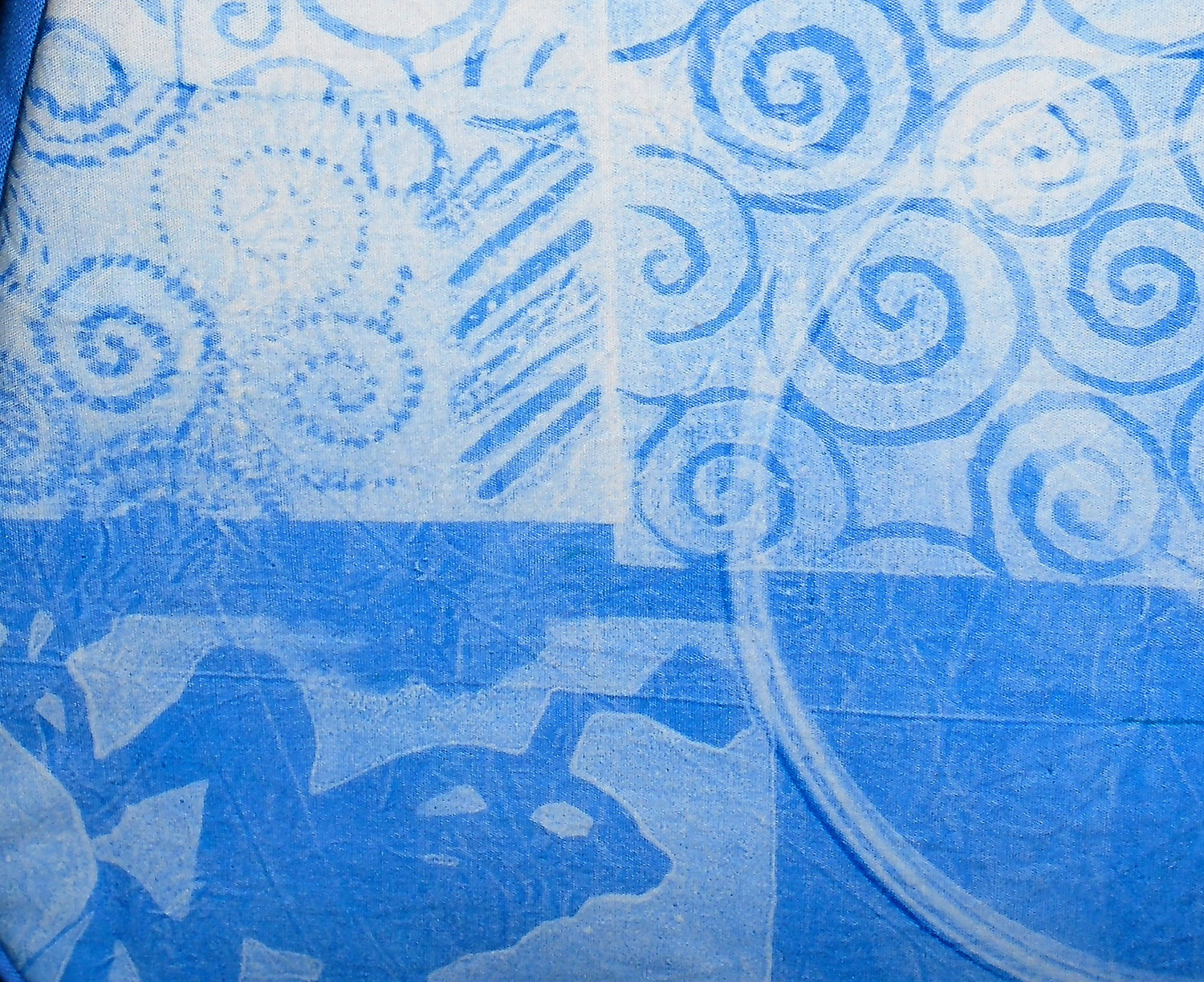 Detail view of monoprinted design on fabric. Frog motif at lower left.