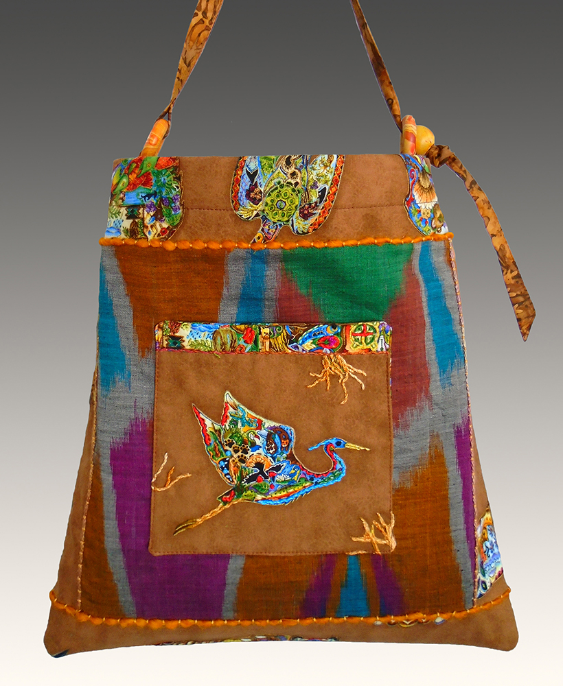 Embroidered heron pocket on square pieced bag with ikat batik from Bali