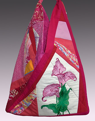 Triangle tote bag, pieced from vintage scraps, heavily machine-embroidered pink callas