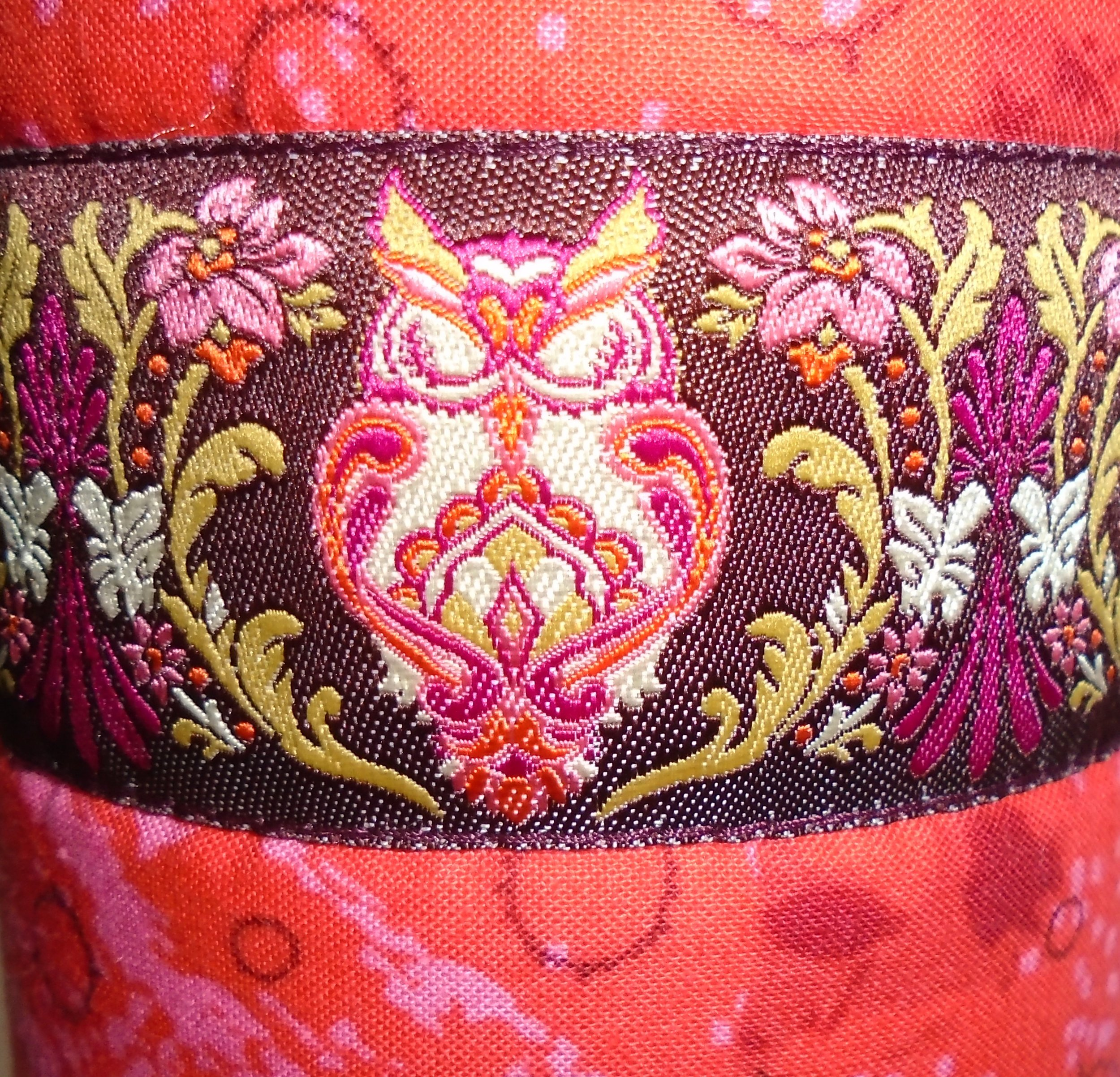 Close-up view of owl design in pink, green, and maroon on ribbon trim of crossbody water bottle carrier.  Australian indigenous print fabric.