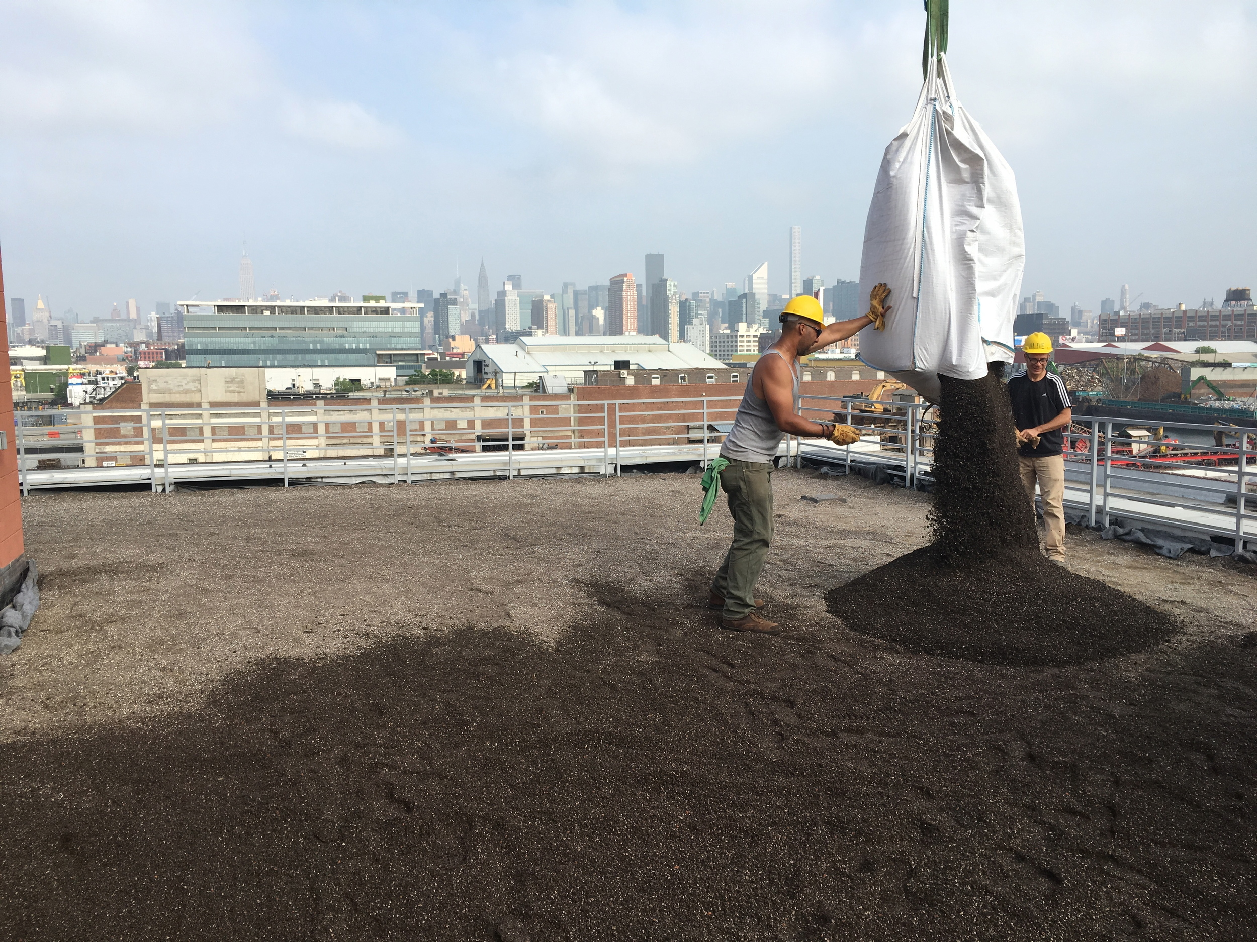 Guiding a crane-suspended one ton bag of soil over the roof.